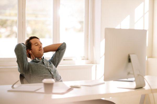 Foto van een professional die relaxed achter zijn bureau zit.