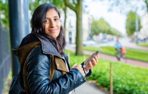 Foto van een jonge vrouw die de sociale kaart bekijkt op haar telefoon.