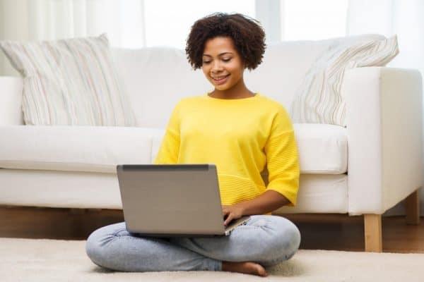 Foto van een vrouw die op de grond zit met een laptop