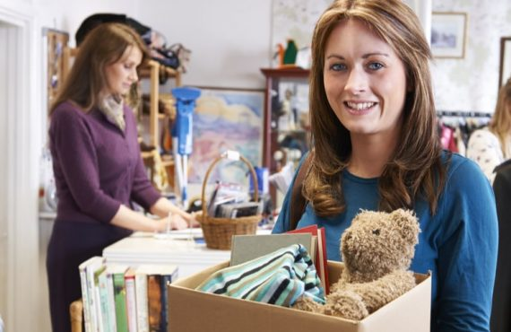 Een vrouw met een doos tweedehands spullen in een kringloopwinkel