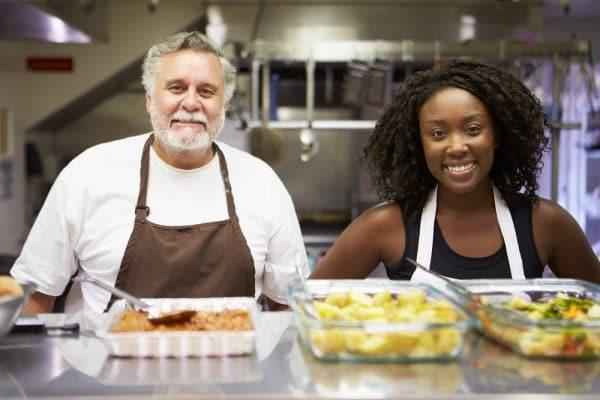 Een man en een vrouw in een keuken achter verschillende schalen met gerechten