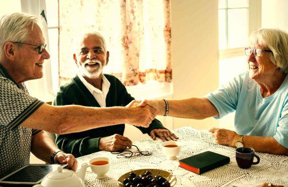 Foto van ambtenaar met tablet en vrouw die elkaar de hand schudden, met toekijkende man aan keukentafel.