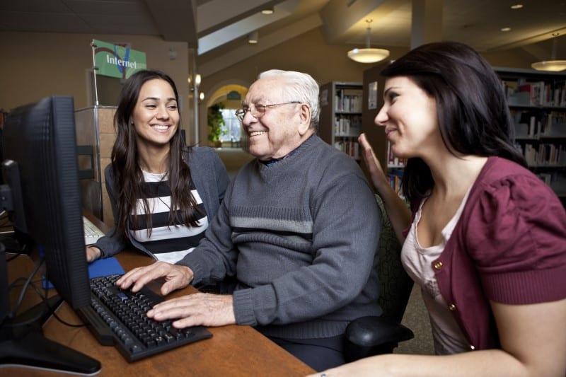 Een oudere man zit in de bibliotheek tussen 2 vrouwen die hem helpen bij het gebruiken van een computer.
