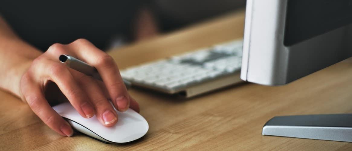 Een rechterhand bedient een muis die bij een toetenbord en monitor in de buurt ligt