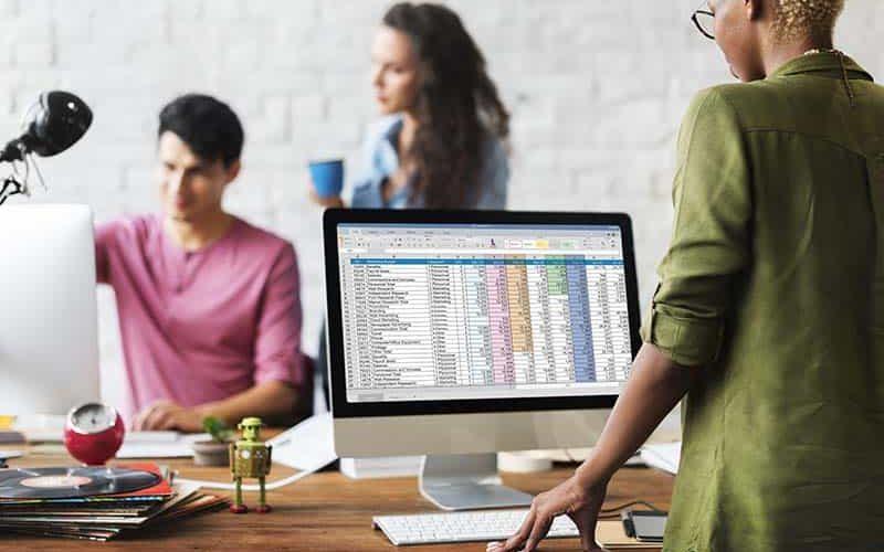 Foto van professionals achter een spreadsheetprogramma op de computer