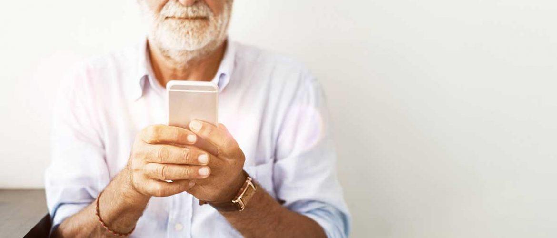Foto van een oudere man die een telefoon bekijkt.