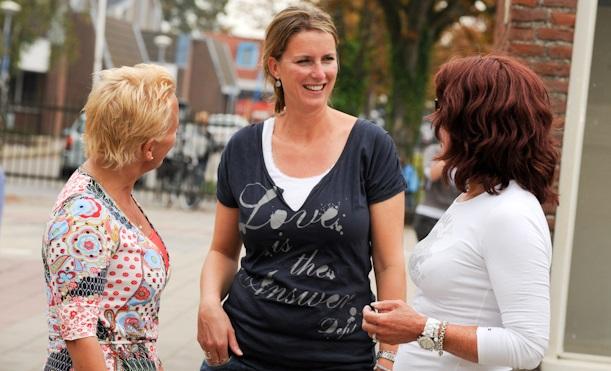 Foto van drie vrouwen in gesprek in de buitenlucht