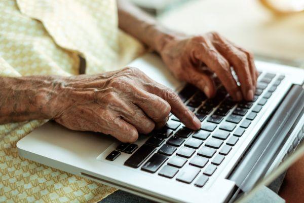 Foto van een oude vrouw die werkt op een laptop