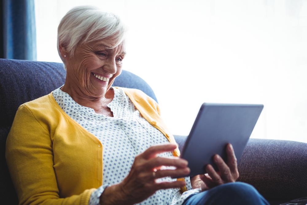 Foto van een vrouw die een tablet gebruikt om iets online op te zoeken.