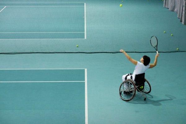 Foto van een tennissende vrouw in een rolstoel