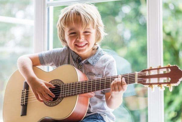 Een jongen van 9 à 10 jaar oud kijkt lachend in de camera terwijl hij akoestische gitaar speelt